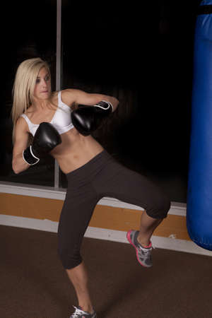 A woman getting ready to lift her foot to kick the bag. photo