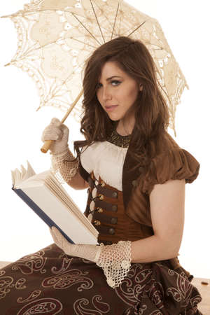 A woman in her vintage dress holding her umbrella while she is reading a book. photo