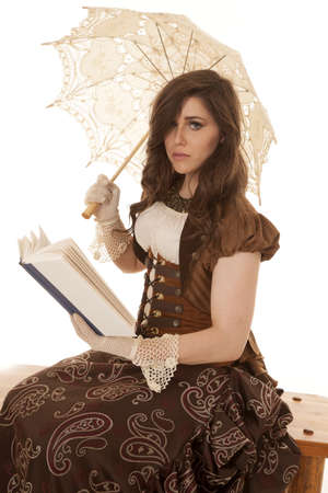 A woman sitting on a bench reading a book and holding onto her umbrella with a sad expression on her face. photo