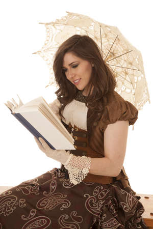 A woman sitting and reading her book with her umbrella with a big smile on her face. photo