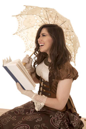 A woman sitting reading a book laughing at something in it. photo