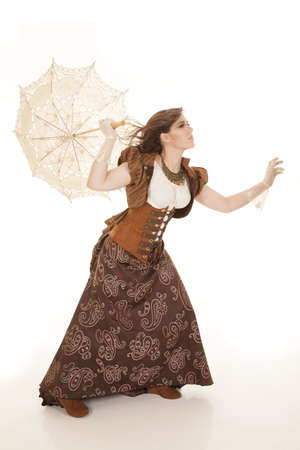 strong: A woman trying to walk in the wind while holding on to her umbrella.