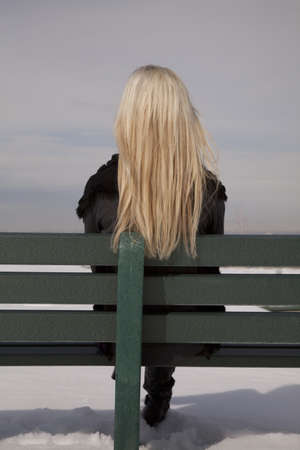 a woman sitting on her green bench with snow on the ground.with her back to the camera. photo