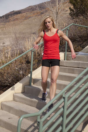 A woman running down the stairs with an intense expression on her face. photo