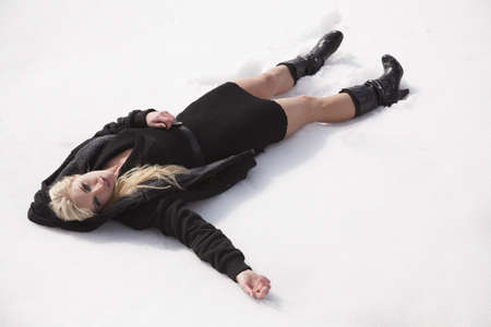 A woman laying in the snow on her back in her black dress.