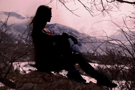 A silhouette of a woman sitting on a rock in nature resting and thinking.