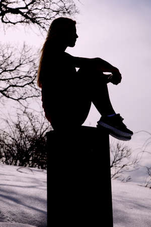 A silhouette of a woman sitting and thinking on a block. photo
