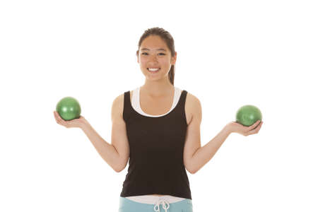 weighted: An Asian woman working out with green weighted balls with a smile on her face.