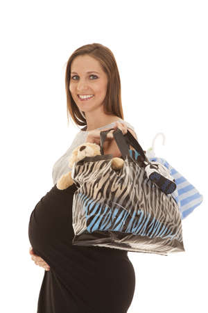 a woman with a smile on her face holding on to her shopping bag. photo