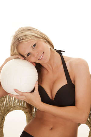 a woman in a black bikini is sitting and holding a volleyball. photo