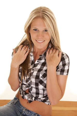 A woman with a smile on her face in her plaid top