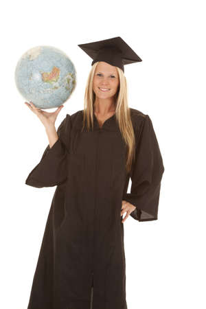 A woman in her cap and gown holding on to a globe photo