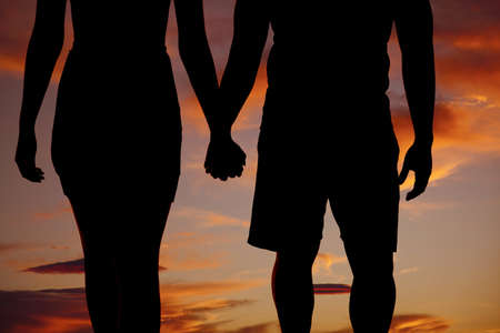 A silhouette of a man and woman holding hands walking