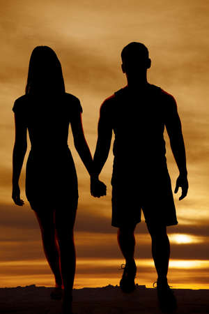 a silhouette of a man and woman holding hands walking. photo