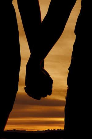 Een close up van een silhouet van een paar hand in hand.