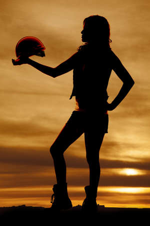 a silhouette of a woman holding on to her hard hat with a beautiful sky behind her. photo