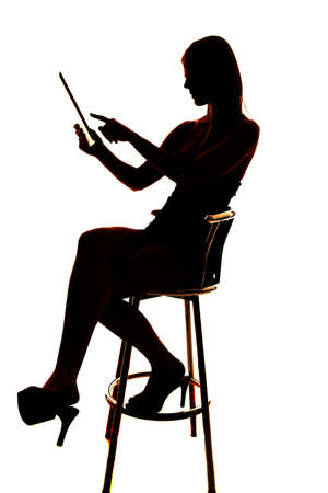 Silhouette of a woman using a tablet pointing. photo