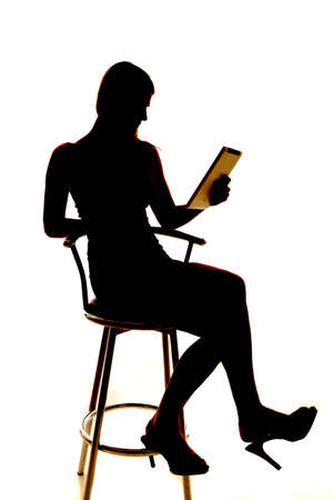 Silhouette of a woman holding a tablet looking at it. photo