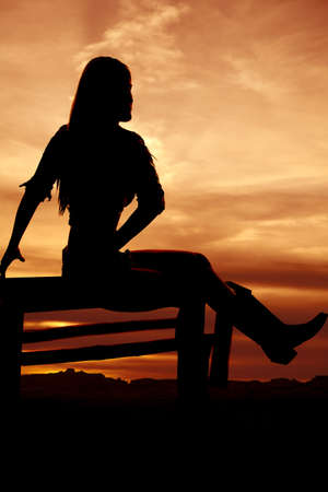 a silhouette of a woman sitting on a bench with a beautiful sky photo