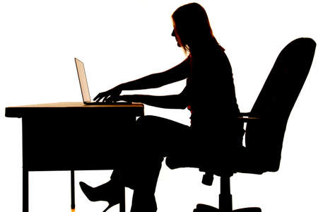 Silhouette of a woman sitting at a desk typing on a computer.