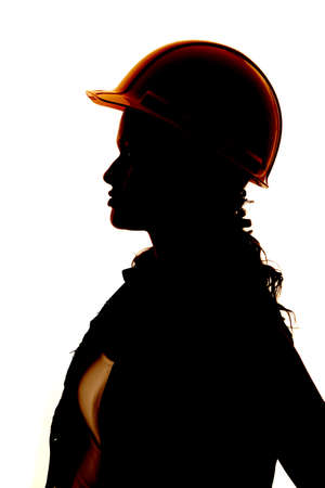 A close up silhouette of a womans face and hard hat