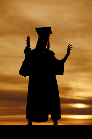 a silhouette of a woman in her cap and gown holding on to her diploma with a beautiful sky behind her photo