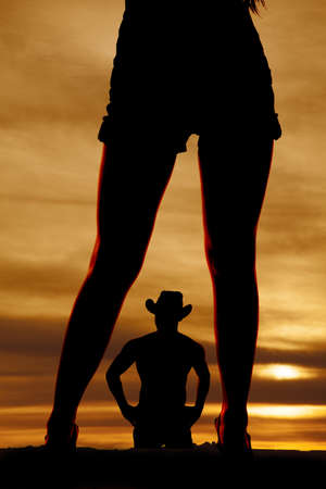 a silhouette of a cowboy in the middle of woman's legs. photo