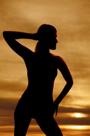 A woman in a bikini is silhouetted in the sunset. photo
