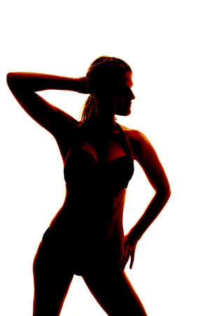 A woman is standing in a bathing suit.  She is a silhouette. photo