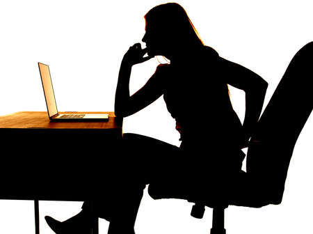 Silhouette of a woman sitting at a desk with a computer thinking.