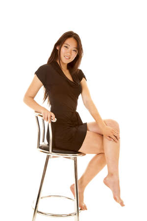 stool: A woman with a smile on her face in her black dress sitting on a stool
