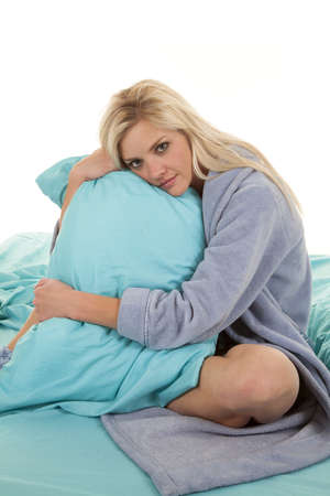 house robe: A woman sitting in her bed in her robe snuggling her pillow.