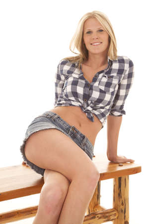 A woman sitting on a bench in her denim skirt and plaid shirt showing off her stomach. photo