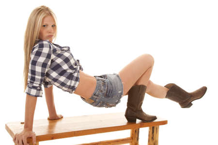 tomboy: A woman pushing herself up on the bench in her skirt and boots. Stock Photo