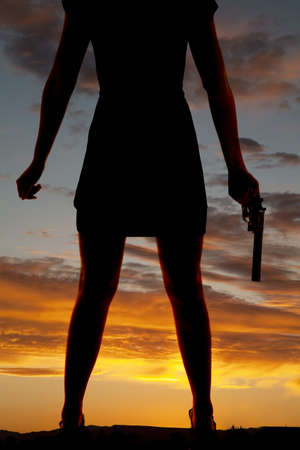 a silhouette of a woman's legs and she is holding a gun in her hand Stock Photo - 20549263