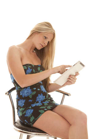 tablet: Woman in a dark flower dress using a tablet serious. Stock Photo