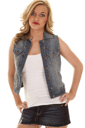 A woman in her denim vest and denim skirt with her hands on her hips photo