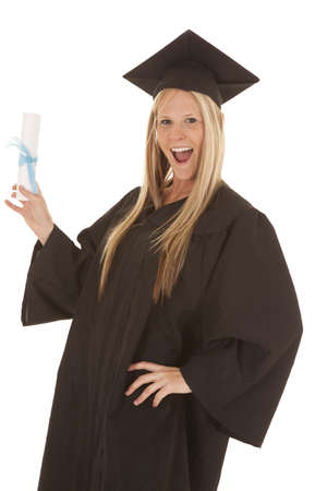 A woman in her cap and gown holding up her diploma with a smile on her face. photo