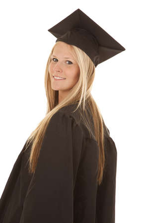 A woman looking over her shoulder in her cap and gown with a smile on her face. photo
