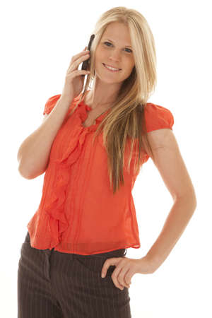 woman on phone: Woman in a red blouse on phone smiling.
