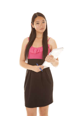 a woman with a serious expression holding on to her pen and binder. photo