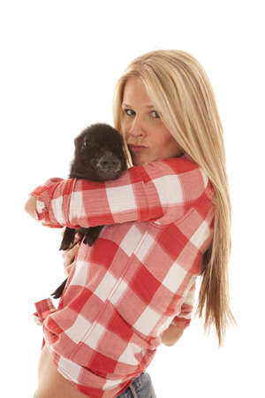 puckered lips: A woman in her red plaid shirt holding on to her pig with puckered lips.