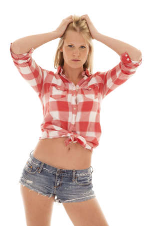 a woman in her red plaid shirt showing off her stomach with her hands in her hair. photo