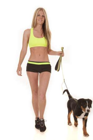 una mujer caminando y haciendo ejercicio, tanto para ella y su perro de montaña suizo.