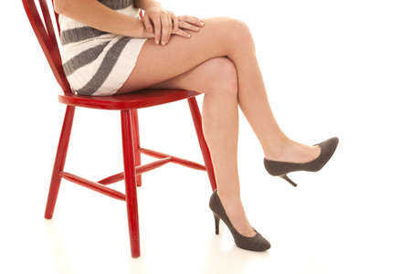 Woman sitting crossed legs in red chair with a striped skirt.