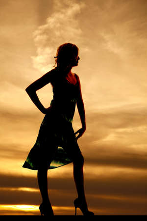 a silhouette of a woman standing in front of a beautiful sky photo