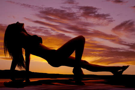 A woman in a bikini silhouetted in the sunset with a reflection in the water. photo