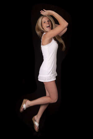 A woman jumping up in the air in her short white dress and shoes Stock Photo - 20966326
