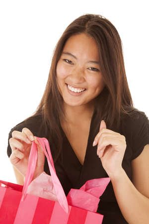a woman with a big smile on her face holding on to her shopping bag. photo
