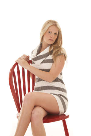 A woman sitting on her red chair in her gray striped dress with a serious expression on her face. photo